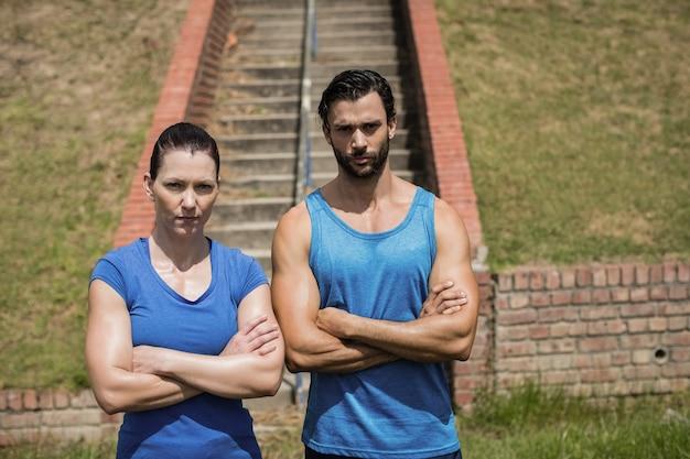 Porträt von fitem mann und frau, die mit verschränkten armen gegen treppe im bootcamp stehen
