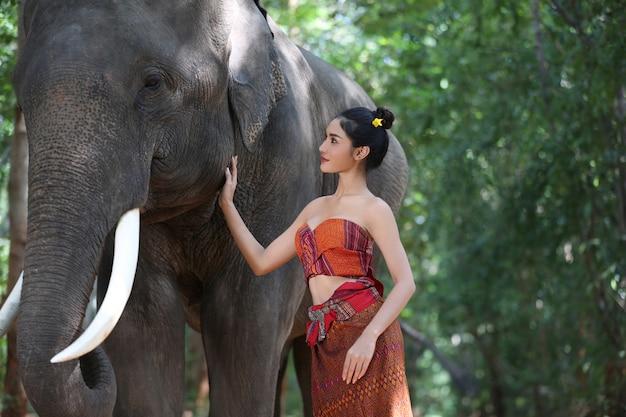 Porträt von frauen im trachtenkleid, das elefanten gegen baum bereitsteht