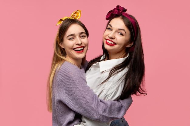 Porträt von freudigen charmanten jungen kaukasischen freundinnen, die spaß haben, lachen, in guter stimmung sind, die sich lokalisiert vor rosa wandhintergrund umarmen
