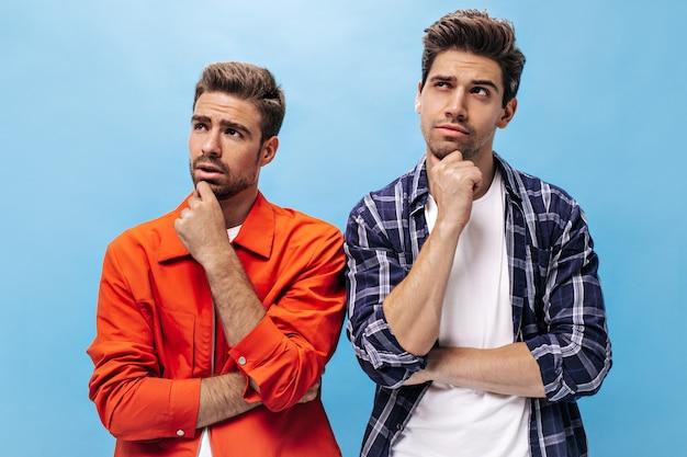 Porträt von freunden, die nach oben schauen. nachdenklicher mann in orangefarbener jacke und mann in kariertem hemd posieren auf blau isolierter wand.