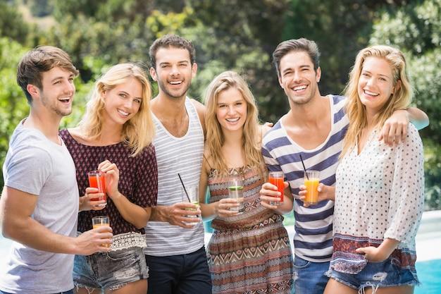 Porträt von freunden, die saft nahe pool trinken
