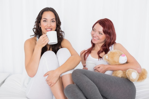 Porträt von freundinnen mit kaffeetassen im bett