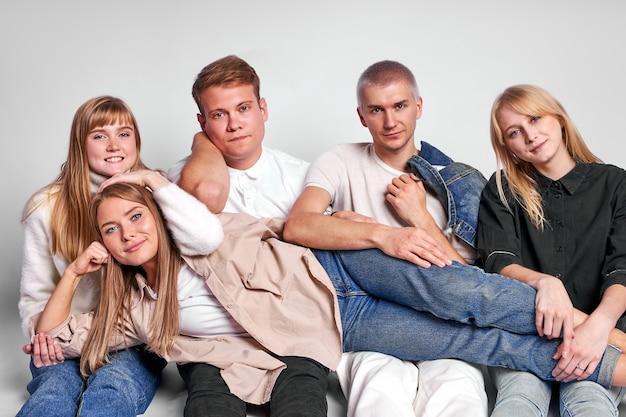 Porträt von freundlichen kaukasischen männern und frauen, die auf dem boden im studio sitzen