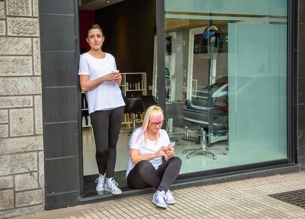 Porträt von friseurinnen in einer kaffeepause mit dem friseur- und schönheitssalon im hintergrund