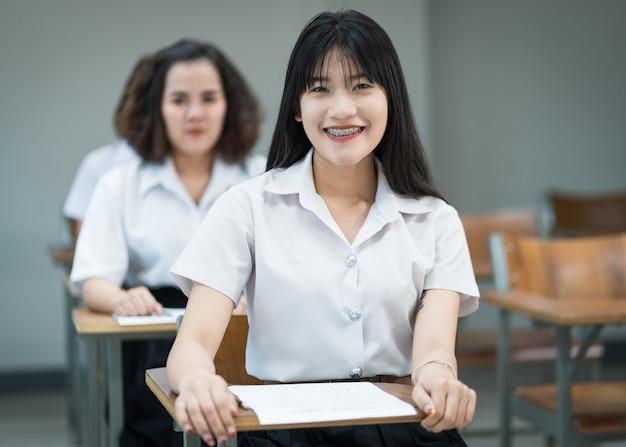 Porträt von fröhlichen asiatischen studentinnen, die im klassenzimmer schreiben und studieren. selektive fous teenager-universitätsstudenten, die im klassenzimmer studieren.