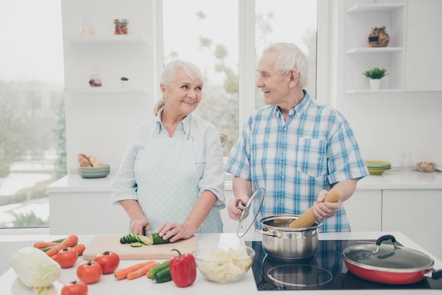 Porträt von fröhlichen ehepartnern beim kochen