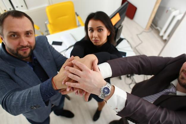 Porträt von fröhlichen jungen geschäftsleuten im büro legen ihre hände übereinander