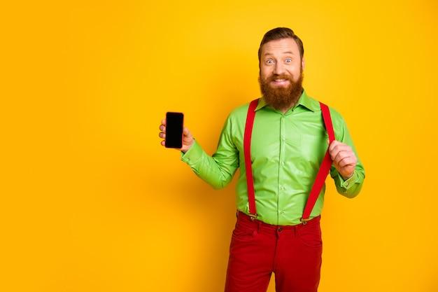 Porträt von fröhlichen mann halten smartphone neue moderne technologie produkt empfehlen promo ziehen stilvolle hosenträger tragen gut aussehende kleidung über gelbe farbe isoliert