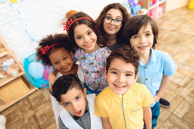 Porträt von frohen kindern in den feiertagshüten an der geburtstagsfeier