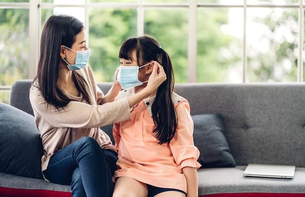 Porträt von genießen glückliche liebe asiatische mutter tragen schutzmaske für kleine asiatische mädchen kind in quarantäne für coronavirus mit sozialer distanzierung zu hause