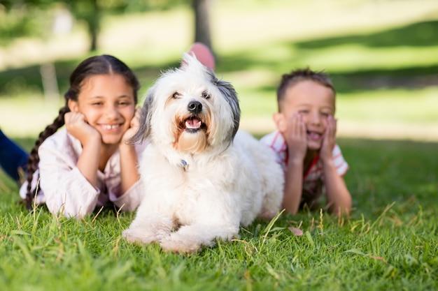 Porträt von geschwistern, die spaß mit ihrem haustierhund haben
