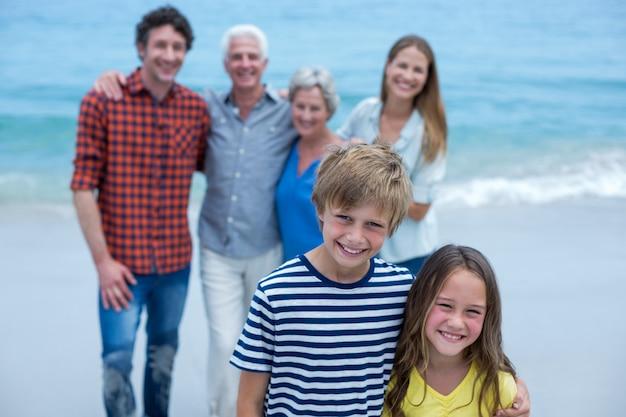 Porträt von geschwistern mit der familie, die im hintergrund steht