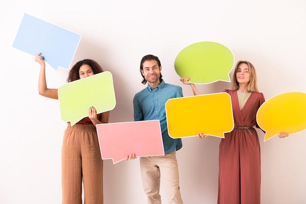 Porträt von gesprächigen jungen multiethnischen leuten, die bunte dialogmarken halten, während sie im internet-chat kommunizieren