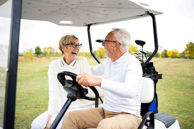 Porträt von gesunden lächelnden älteren paaren, die golfauto fahren und in die grüne zone gehen.