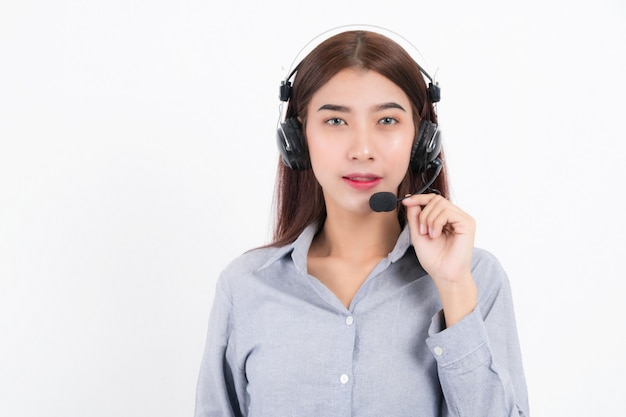 Porträt von glücklich lächelnden weiblichen kundensupport-telefonistin kurzes haar, ein weißes hemd mit headset tragend, das auf einer seite steht und den kopfhörer isoliert auf weißem hintergrund hält.