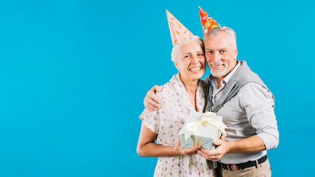 Porträt von glücklichen älteren paaren mit geburtstagsgeschenk auf blauem hintergrund