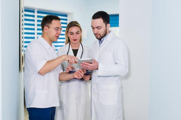 Porträt von glücklichen cowerkers mit klemmbrett bei der stellung am krankenhaus