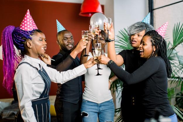 Porträt von glücklichen jungen afrikanischen freunden, die die brille miteinander berühren und geburtstag feiern
