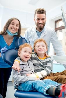 Porträt von glücklichen jungen, die mit zahnarzt und assistentin in der zahnarztpraxis auf dem stuhl sitzen