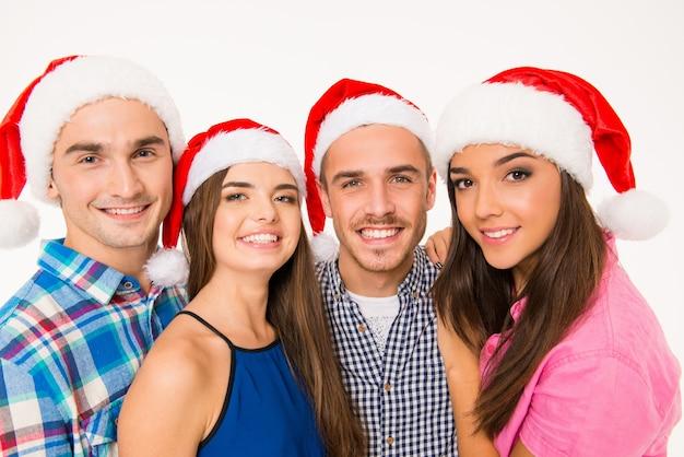 Porträt von glücklichen jungen freunden in weihnachtsmützen