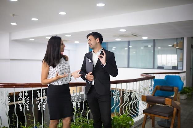 Porträt von glücklichen jungen kollegen oder von partnern, die in der halle sprechen