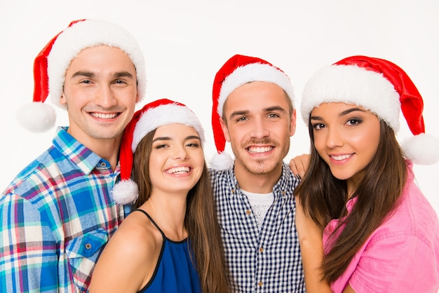 Porträt von glücklichen jungen leuten in weihnachtsmützen