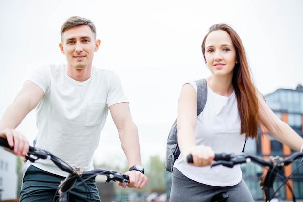 Porträt von glücklichen jungen paaren auf fahrrädern