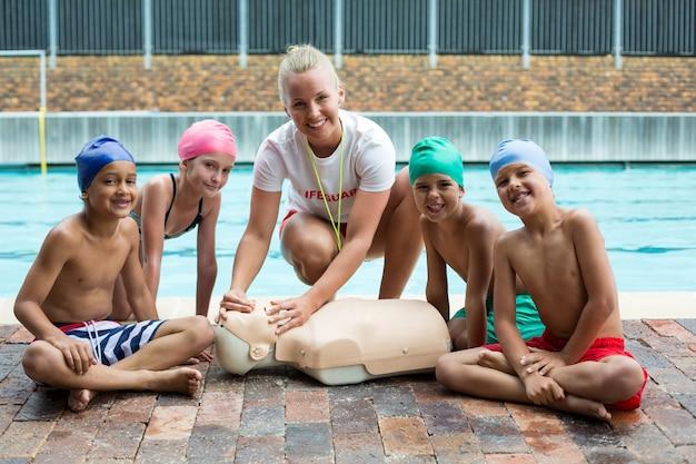 Porträt von glücklichen kindern und ausbilder während des rettungstrainings am pool