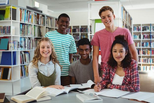 Porträt von glücklichen klassenkameraden, die in der bibliothek studieren