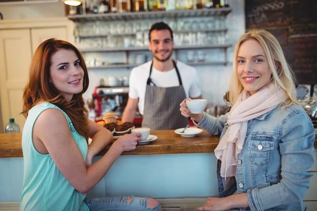 Porträt von glücklichen kunden mit kellner an der kaffeestube