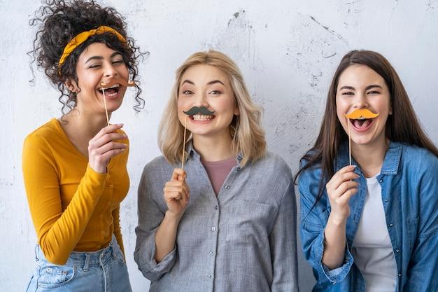 Porträt von glücklichen lachenden frauen mit schnurrbärten