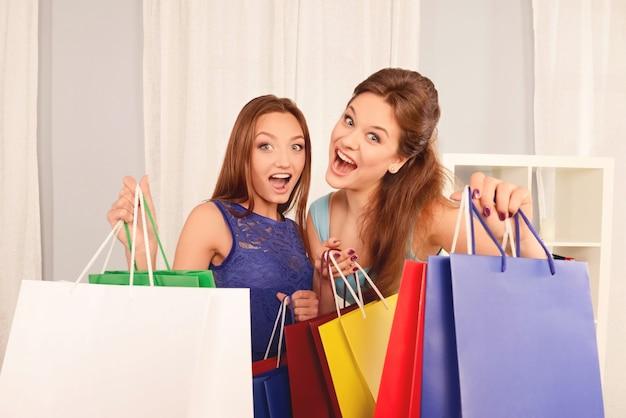 Porträt von glücklichen schwestern, die packungen mit neuen kleidern halten