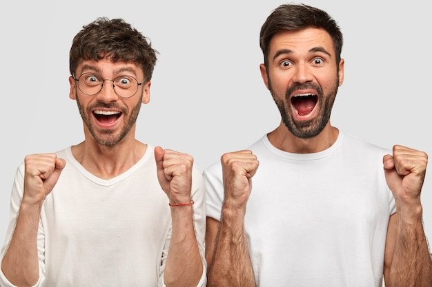 Porträt von glücklichen überglücklichen bärtigen männern, die fäuste ballen und freudig ausrufen, positivität ausdrücken, erfolg freuen, in weißen lässigen t-shirts gekleidet, nebeneinander stehen. erfolgskonzept