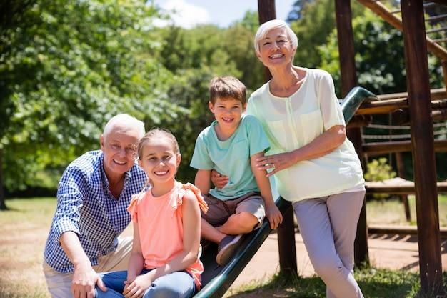 Porträt von großeltern, die mit ihren enkelkindern im park spielen