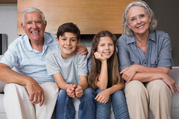 Porträt von großeltern und von zwei kindern, die zu hause auf sofa im wohnzimmer sitzen