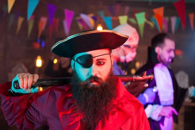 Porträt von gutaussehenden männern, die bei halloween-versammlung wie ein trauriger pirat verkleidet sind. attraktiver mann in einem piratenkostüm.