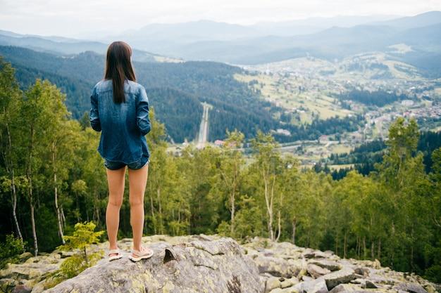 Porträt von hinten des brunettemädchens stehend im mountaing mit schönem landschaftspanorama.