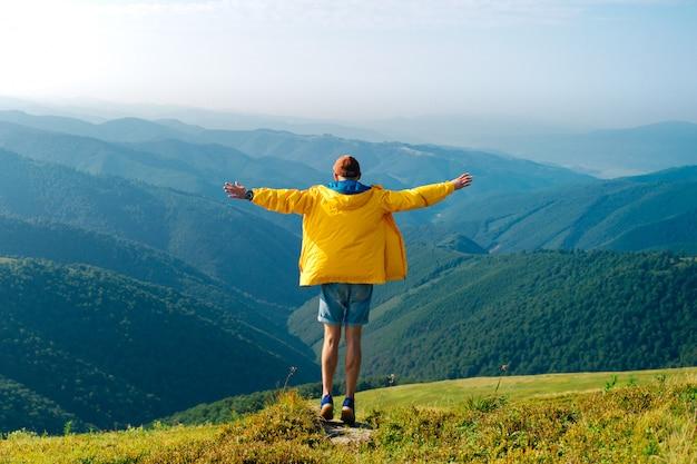 Porträt von hinten des menschen, der freiheit und fabelhafte landschaft in den bergen genießt.