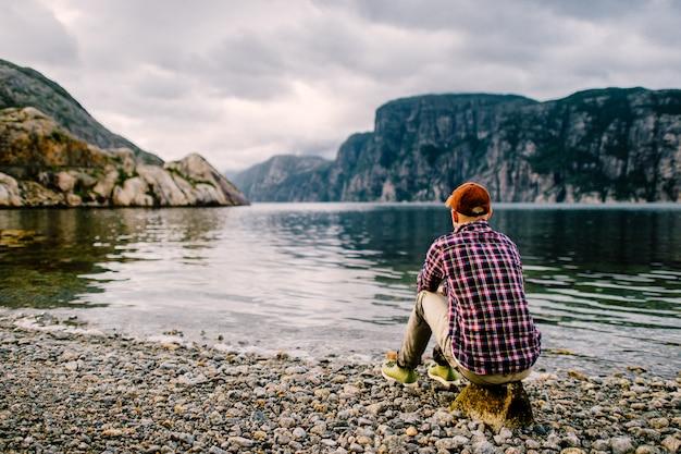 Porträt von hinten des reisendenmannes, der auf stein am fjord in norwegen sitzt und fabelhafte naturlandschaft genießt.