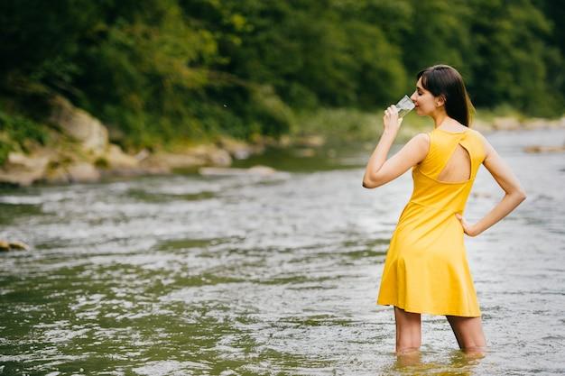 Porträt von hinten des sexy brunettemodells im gelben kleid, das im sommerfluß mit einem glas wasser in ihrer hand steht.