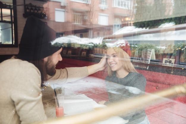 Porträt von hipstern im café hinter dem glas