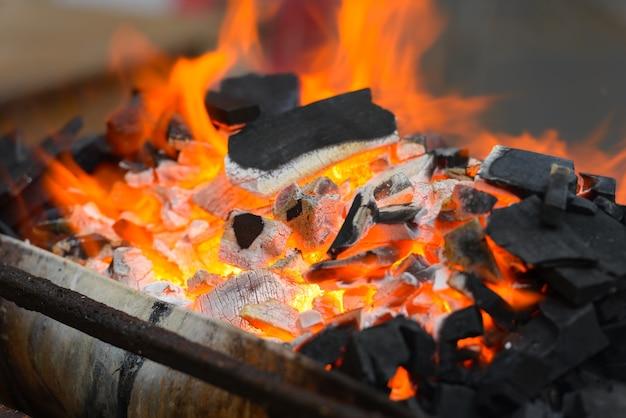 Porträt von holzkohle, die mit feuer brennt, bereit zum grillen und grillen