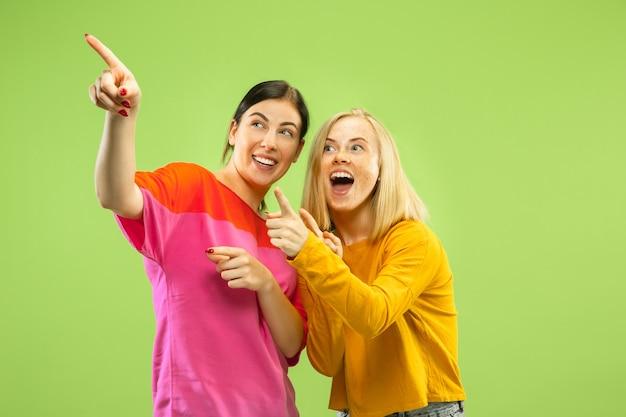 Porträt von hübschen bezaubernden mädchen in lässigen outfits lokalisiert auf grünem studiohintergrund. zwei weibliche models als freundinnen oder lesben. konzept von lgbt, gleichheit, menschlichen emotionen, liebe, beziehung.