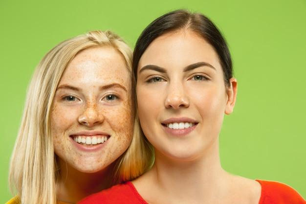 Porträt von hübschen charmanten mädchen in lässigen outfits lokalisiert auf grüner wand. zwei weibliche models als freundinnen oder lesben. konzept von lgbt, gleichheit, menschlichen emotionen, liebe, beziehung.