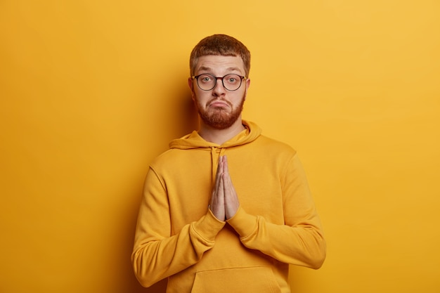 Porträt von hübschen drückt handflächen, macht gebetsgeste, bittet um hilfe, spitzt lippen und sieht ernst aus, gekleidet in lässigen hoodie, isoliert über gelber wand. bitte tu mir einen gefallen