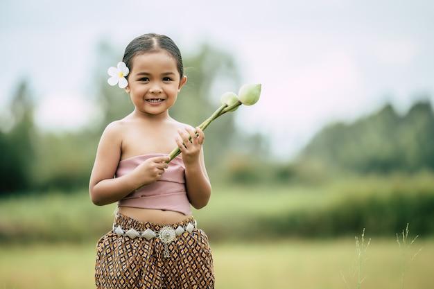 Porträt von hübschen kleinen mädchen in traditioneller thai-kleidung und weiße blume auf ihr ohr legen, zwei lotus in der hand auf reisfeld stehen und halten