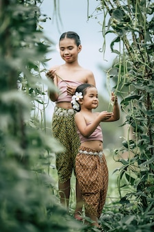 Porträt von hübschen mädchen in traditioneller thailändischer kleidung und weiße blume an ihrem ohr, stehend im pflanzenhof mit langen bohnen, sie lächeln vor glück
