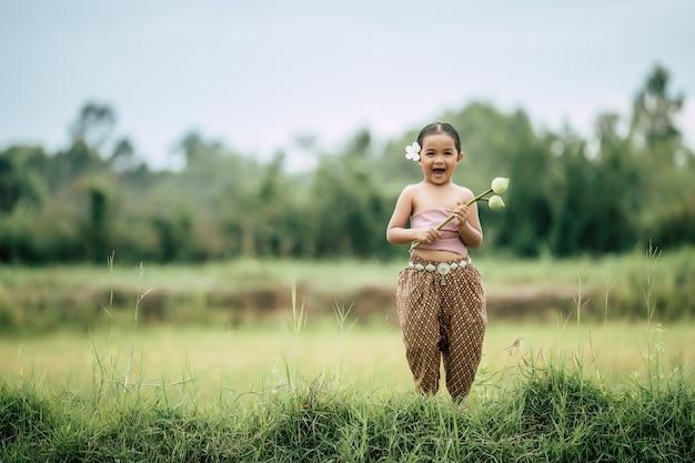 Porträt von hübschen mädchen in traditioneller thailändischer kleidung und weiße blume an ihrem ohr, stehend und zwei lotus in der hand auf reisfeld halten, sie lacht vor glück, kopienraum