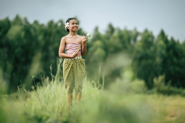 Porträt von hübschen mädchen in traditioneller thailändischer kleidung und weiße blume auf ihr ohr, stehend und zwei lotus in der hand auf reisfeld halten, sie lächelt glücklich, kopienraum