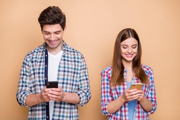 Porträt von ihm er sie sie schöne attraktive schöne konzentrierte konzentrierte konzentrierte süchtig fröhliche fröhliche paar tragen kariertes hemd mit 5g app isoliert über beige pastellfarbe hintergrund